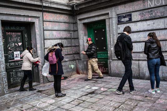 Des Bruxellois s'arrêtent pour photographier les messages de soutien  aux victimes qui recouvrent les murs dans le quartier  de la Bourse, devenu un lieu de recueillement.