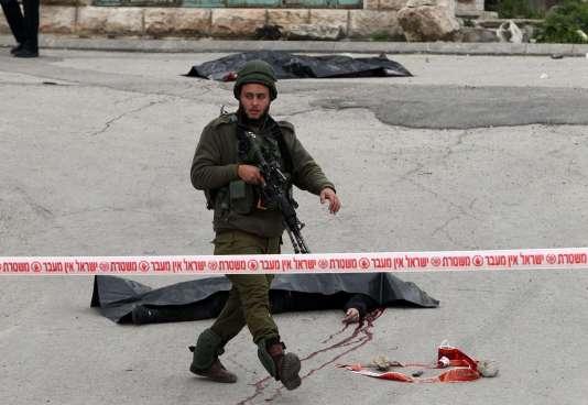 Un soldat garde les corps des deux Palestiniens qui ont été tués après avoir attaqué un militaire israélien, le 24mars, à Hébron.