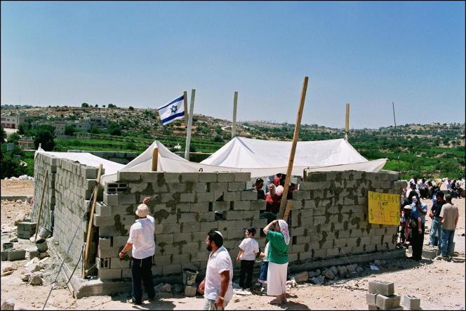 Des colons israéliens travaillent à la construction d'une maison bâtie illégalement près de la colonie de Qiryat Arba, en Cisjordanie.