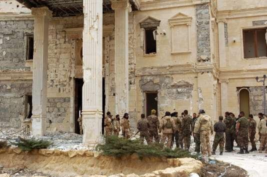 Des troupes de l'armée syrienne avancent vers un bâtiment appartenant à la famille royale qatarie, dans la périphérie de Palmyre, le 24 mars 2016.