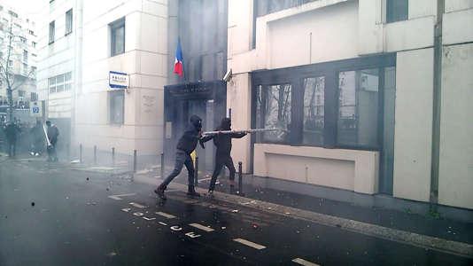 Capture d'écran d'une vidéo montrant des casseurs qui s'en prennent à un commissariat de police à Paris, vendredi 25 mars. AFP / Guillaume Bonnet
