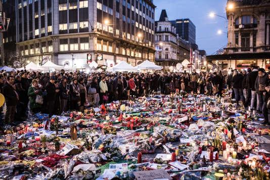 Fleurs, bougies et drapeaux de toutes nationalités sont déposés au sol face à la Bourse de Bruxelles, le 24mars.