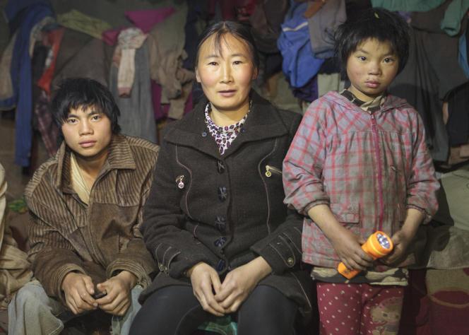 Li Huanming (à gauche) avec sa voisine et sa jeune sœur, le 9 décembre 2015 dans la ville de Bijie (district de Nayong, province de Guizhou, Chine).