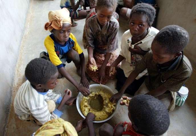 Des écoliers prennent leur repas dans la cour de l'école du village de Kokolo, près de Bandiaga. Mali, 2002.