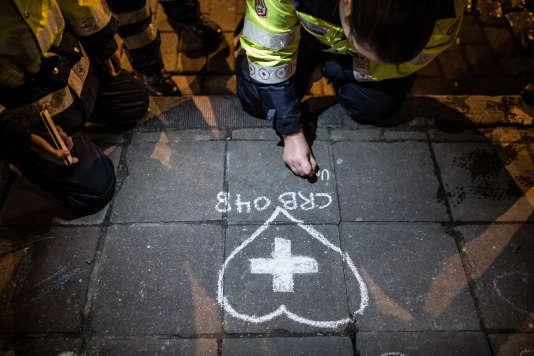 Des membres de la Croix-Rouge dessinent sur le parterre devant la Bourse, à Bruxelles. Plus de 200secouristes ont pris part au rassemblement le 25mars.