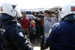 Migrants stand in front of Greek police officers during the protest demanding the opening of the border between Greece and Macedonia in the northern Greek border station of Idomeni, Greece, Tuesday, March 29, 2016. More than 15,000 people - nearly a third of the total stranded in Greece - are refusing to move to government-built shelters around the country, and remain at the border with Macedonia and at the port of Piraeus, near Athens. (AP Photo/Darko Vojinovic)