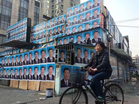 Une chinoise passe devant  une maison recouverte de posters du président  Xi Jinping à Shanghai le 26 Mars.