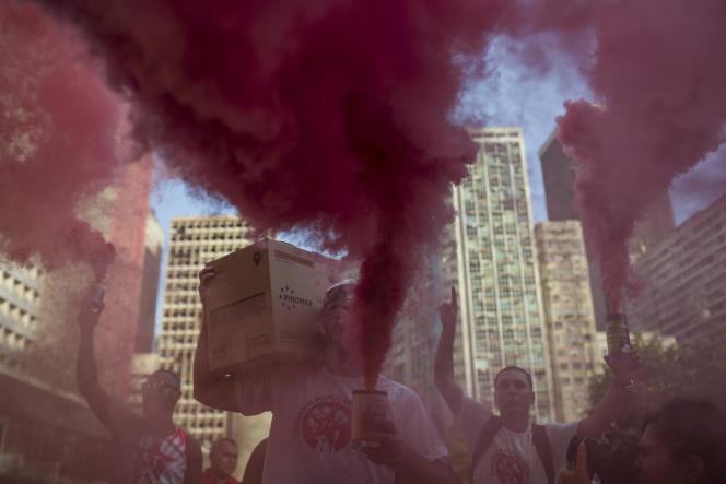 Des manifestants dans un nuage de fumée rouge, couleur du Parti des Travailleurs auquel appartieneent Lula et Dilma Roussef, lors d'un manifestation en soutien à la présidente brésilienne, le 31 mars 2016 à Rio de Janeiro.