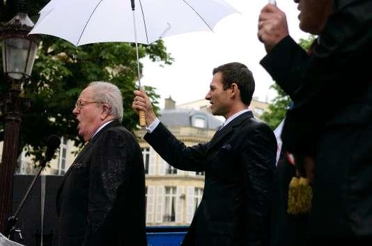 Jean-Marie Le Pen chante la Marseillaise, sous un parapluie tenu par Gérald Gérin,  à la fin d'un rassemblement du Front National devant l'Assemblée Nationale pour le rétablissement de la peine de mort pour les crimes les plus graves, à la suite des meurtres de deux enfants le 20 mai 2006