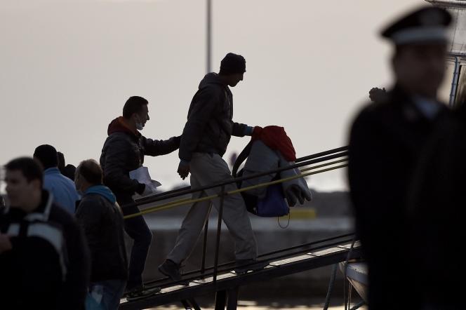 Des migrants embarquent à bord d'un bateau turc dans le port de Mytilène, lundi 4 avril.