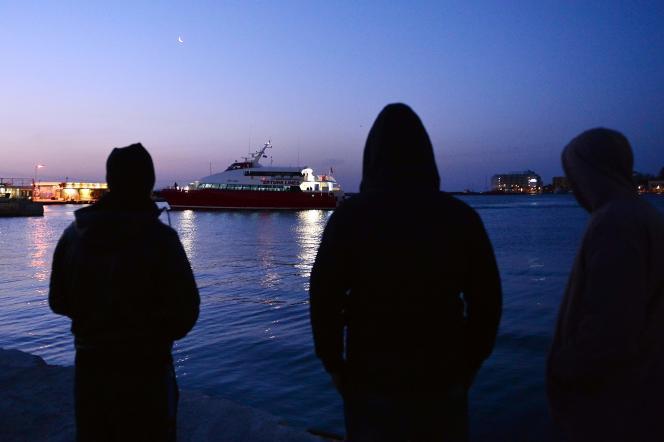 Des réfugiés sur le port de Chios observent le bateau qui va ramener en Turquie le premier groupe de migrants expulsés de Grèce, le 4 avril 2016.