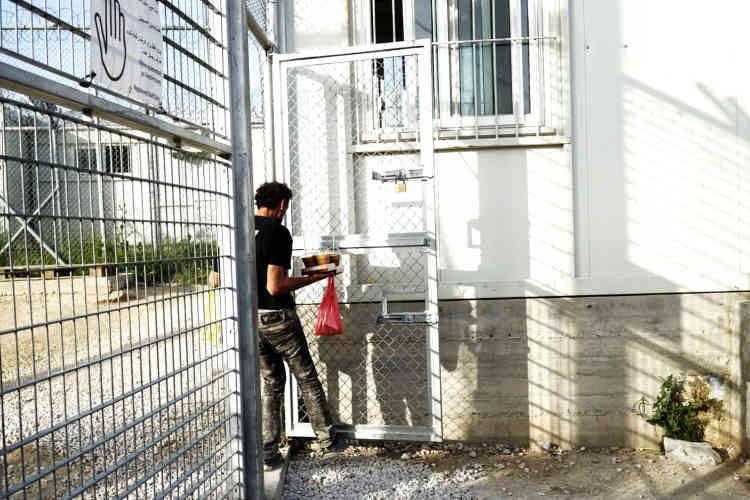 Un homme apporte des cafés aux policiers présents à Moria, le 4 avril.