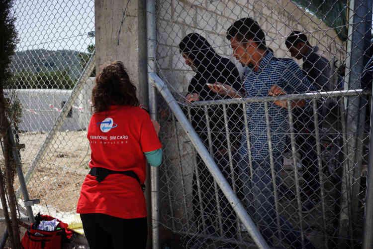 Une Grecque vend des cartes téléphoniques aux migrants à travers la clôture du hotspot de Moria.