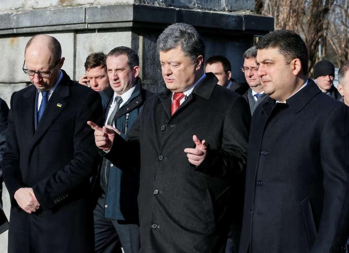 Le président ukrainien Petro Poroshenko (au centre) aux côtés de l'ancien premier ministre, Arseny Iatseniouk (gauche) et du nouveau, Volodymyr Groïsman (droite) à Kiev, le 29 janvier 2016