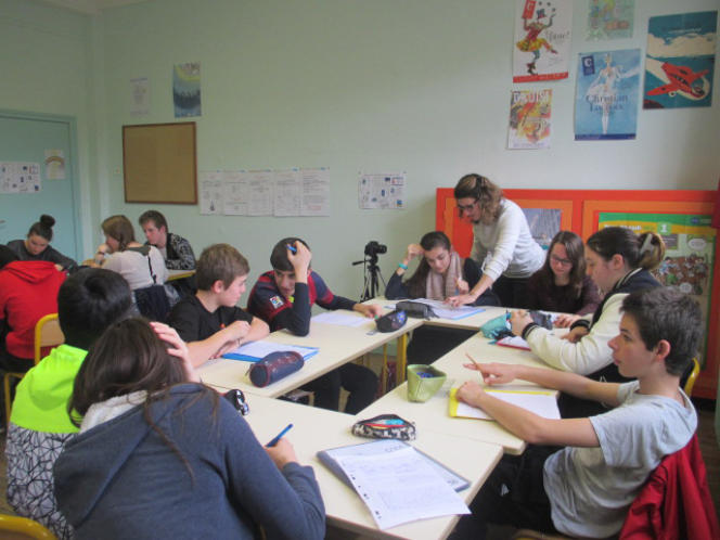 Emilie Tardes, professeure d'histoire-géo, fait des remarques au groupe devant rédiger le deuxième couplet de la chanson, dévolu au voyage des migrants.