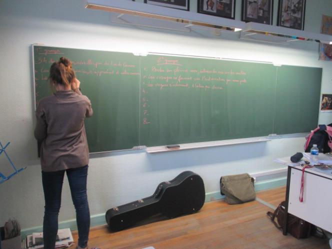Une élève écrit les premières phrases de la chanson.