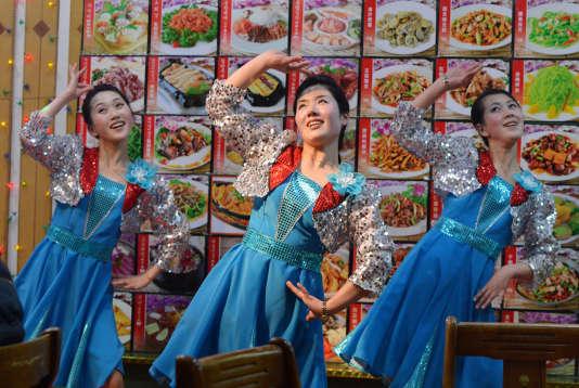 Sur cette photo prise en février 2013, des serveuses nord-coréennes dansent devant les clients d'un restaurant proposant des spécialités de leur pays et situé à Dandong, en Chine, le long de la frontière.