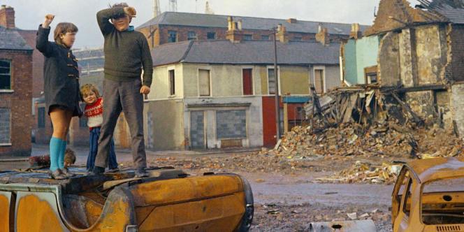 Des enfants jouent sur les carcasses de voitures calcinées dans un quartier de Belfast, en février 1972.