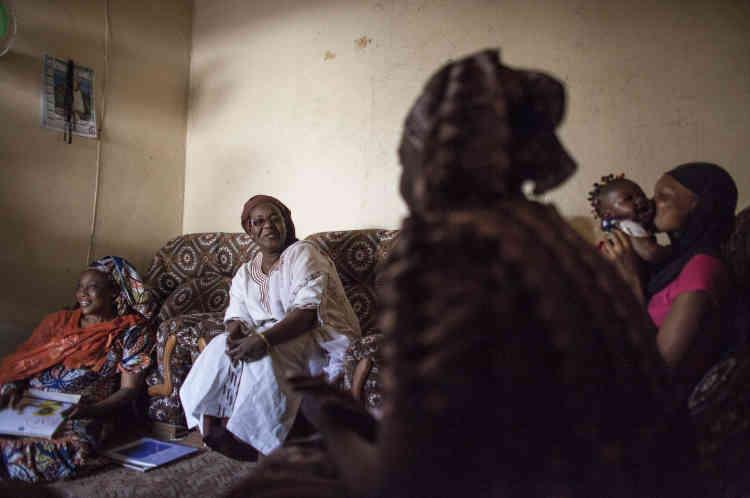 Khadijah Drame (à gauche) et Fatou Hane (au centre) discutent avec la famille Dieynaba Tall.