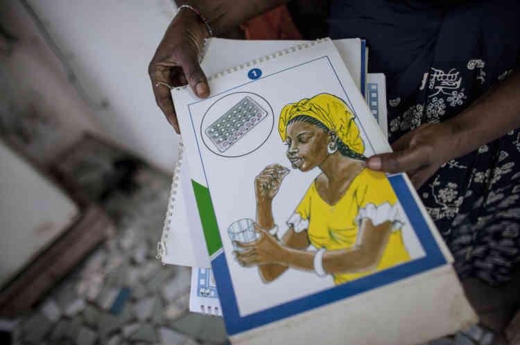 Khadijah Drame, une des marraines de quartier, montre un dessin destiné à expliquer l'utilisation d'un contraceptif.