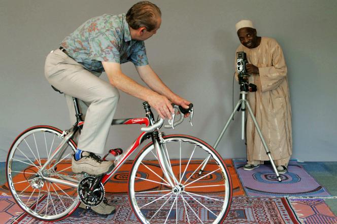 Le photographe malien Malick Sidibé, portraitiste reconnu, prend une photo de l'ancien champion cycliste Damien Salmon, le 12 juillet 2006 à Plouha, en Bretagne.