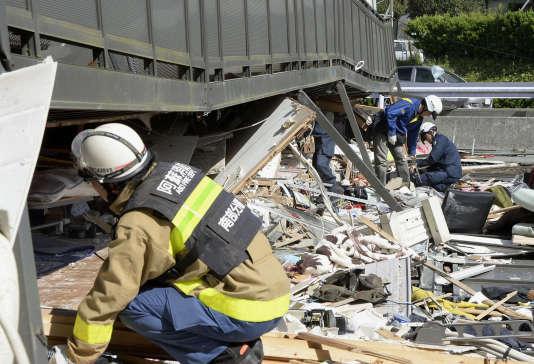 La police et les pompiers tentent d'extraire des personnes coincées dans les décombres d'un appartement dont le premier étage a été détruit par le séisme à Minamiaso, le 16 avril 2016.