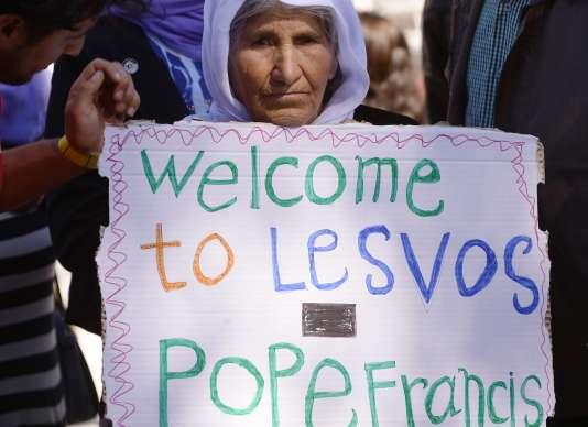 """Une femme accueille le pape François avec une pancarte """"Bienvenue à Lesbos, pape François"""", le 16 avril au camp de réfugiés de Moria."""