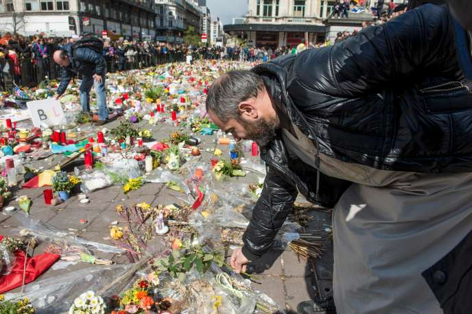 Un homme dépose des fleurs sur le mémorial de fortune de la place de la Bourse, à Bruxelles, le 17 avril 2016.
