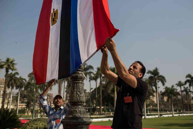Des employés installent des drapeaux aux couleurs de l'Egypte et de la France dans les jardins du palais de Qubbah, auCaire.