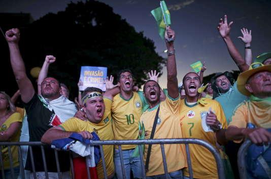 Des Brésiliens aux couleurs du camp en faveur de la destitution de Dilma Rousseff regardent en direct le vote des députés, dimanche 17 avril.