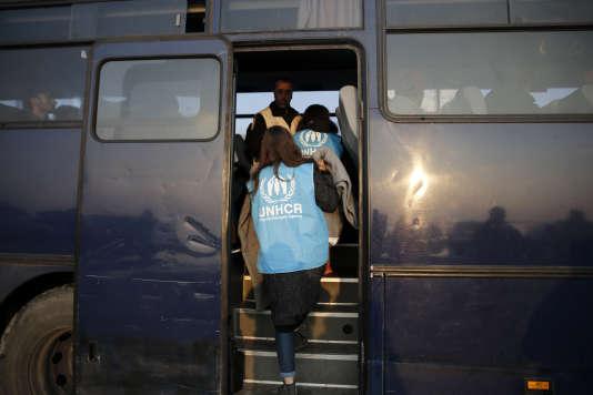 Des bénévoles du Haut-Commissariat des Nations unies pour les réfugiés montent dans un bus des gardes-côtes grecques pour rencontrer des migrants, en mars.