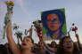 """Des femmes brandissent des fleurs lors de la manifestation """"Fleurs pour la démocratie"""", contre la destitution de Dilma Rousseff, face au palais présidentiel de Planalto, à Brasilia, le 19 avril 2016."""