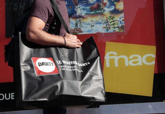 Un homme portant un sac Darty devant une enseigne Fnac, à Nice, en 2015.