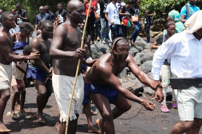 Un comédien dans le rôle d'un habitant de Bimbia (Cameroun) est conduit, enchaîné, vers un navire pour servir d'esclave dans le cadre de la traite transatlantique.