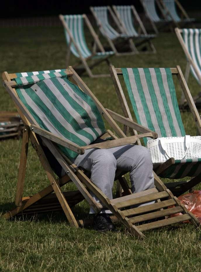 Obstacle, et non des moindres, il faut obtenir l'accord de l'employeur pour passer à temps partiel (Photo: A Hyde Park, à Londres, une femme se protège du soleil à l'aide d'une chaise longue).