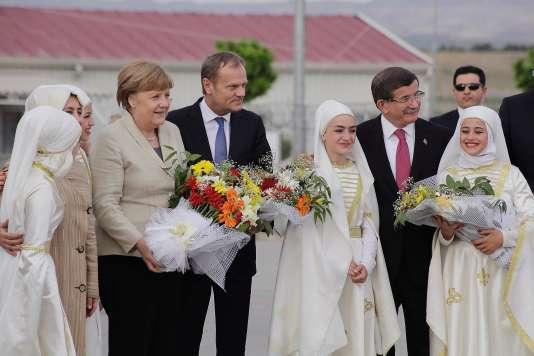 """Angela Merkel, Donald Tusk et le premier ministre turc Ahmet Davutoglu lors de la visite d'un """"camp modèle"""" pour réfugiés syriens à Gaziantep en Turquie le 23 avril 2016."""
