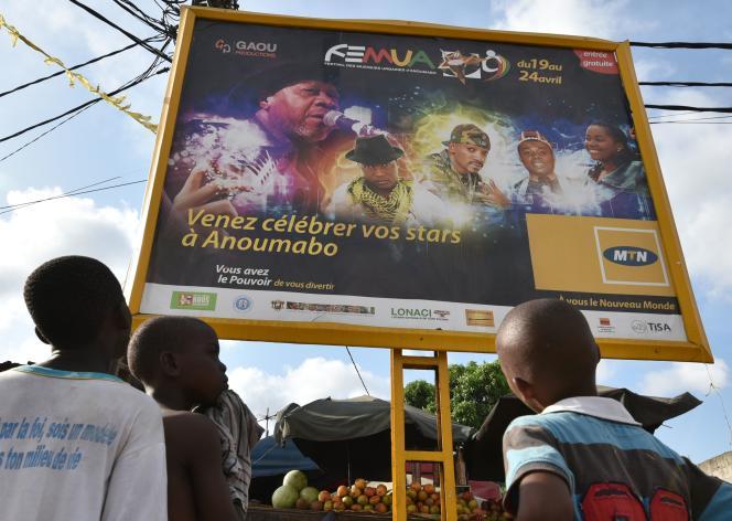 Des enfants regardent une affiche du festival FEMUA d'Abidjan, auquel se produisait Papa Wemba, le 24 avril, et où il est décédé sur scène.