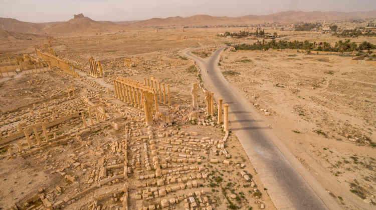 Vue depuis un drone de la cité antique de Palmyre en plein désert et, à droite de la route, l'oasis et la ville moderne.