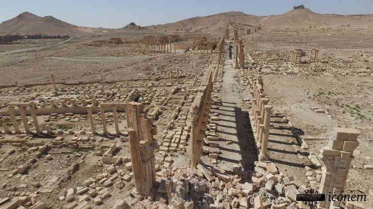 Panorama d'entrée de l'antique Palmyre. Au premier plan, l'arc de triomphe écroulé et la longue colonnade. Au fond à gauche, l'enceinte du temple de Bêl, et tout au fond, à flanc de colline, la nécropole millénaire.