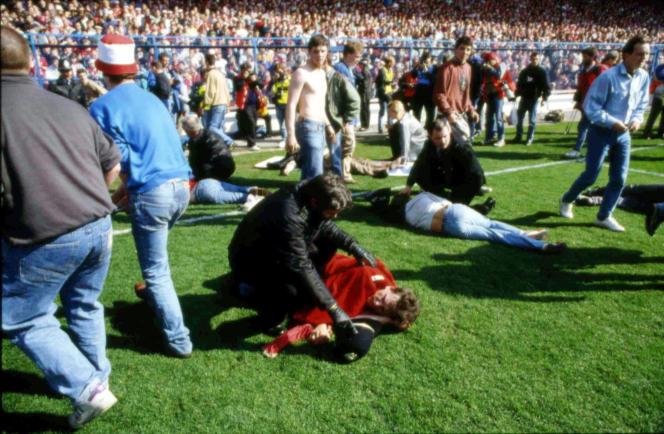 Photo d'archive montrant des personnes portant secours à des blessés dans le stade de Hillsborough, le 15 avril 1989.