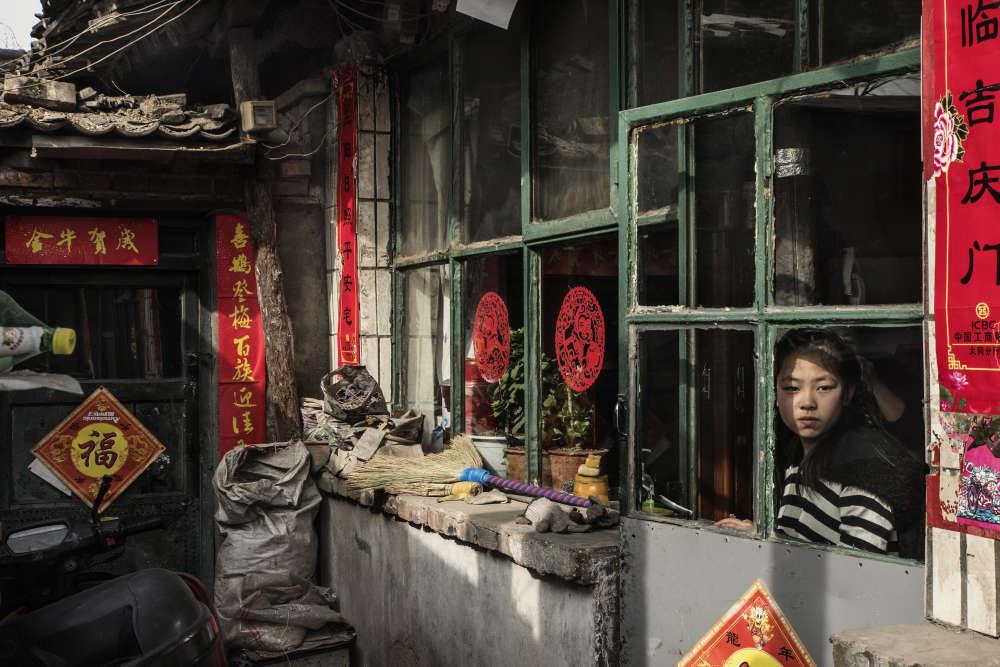 Une jeune fille à sa fenêtre dans une maison traditionnelle du centre de Datong. La maison est promise à la démolition et ses habitants doivent être relogés dans le cadre du projet de transformation de la ville. Le chantier a été interrompu alors que la ville est endettée de près de 2milliards de dollars. Les derniers habitants du centre-ville ne savent pas s'ils doivent partir, ni quand.