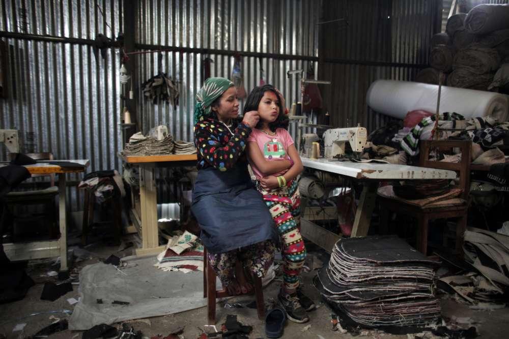 Maya Pariyar, 39 ans, coupe les cheveux  de sa fille Nirmala, 8 ans, dans une usine de textile de Katmandou, le 28 mars. Nirmala a perdu sa jambe lors du tremblement de terre, elle n'est pas retournée à l'école depuis.