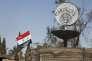 """""""Si l'on veut mener l'offensive contre des voyous devenus terroristes en s'attaquant au financement de leurs actions, il faut se focaliser en priorité sur l'économie criminelle qui irrigue les «écosystèmes» délétères dans lesquels ils évoluent à leur aise"""" (Photo: le drapeau national syrien flotte à coté d'un slogan de Daech à un rond-point où se sont tenues des exécutions perpétrées par l'organisation Etat islamique à Palmyre  le 1er avril)."""