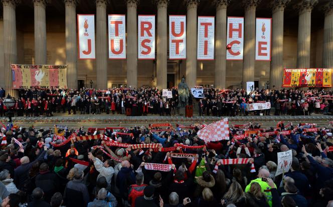 Des manifestants chantent l'hymne du club de Liverpool, «You'll never walk alone», à Liverpool, mercredi 27 avril 2016, pendant un hommage aux victimes de la tragédie du stade d'Hillsborough.