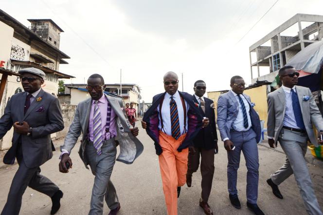 Des sapeurs démontrent leur élégance en arpentant une rue de Kinshasa.