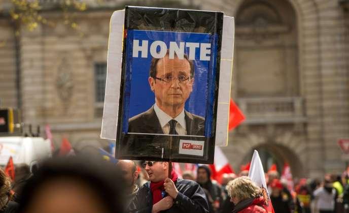 Un homme porte une pancarte avec un portrait de François Hollande sur laquelle on peut lire