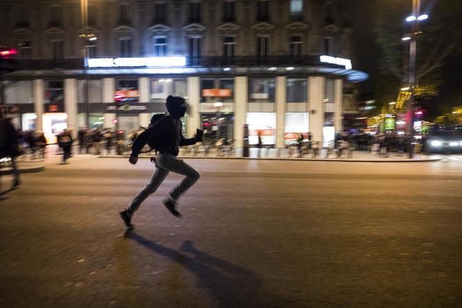 Une personne court en raison d'échauffourées avec les forces de l'ordre, le 28 avril 2016 sur la place de la République à Paris, lors de la Nuit debout.