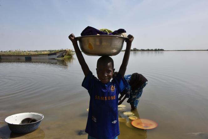 Un enfant porte des vêtements lavés dans le lac Tchad, à Bol.