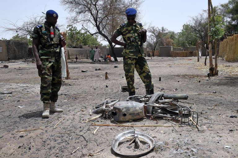 Des gendarmes tchadiens  examinent une moto détruite à N'Gouboua, dans les environs du lac Tchad, le 6 avril 2015.