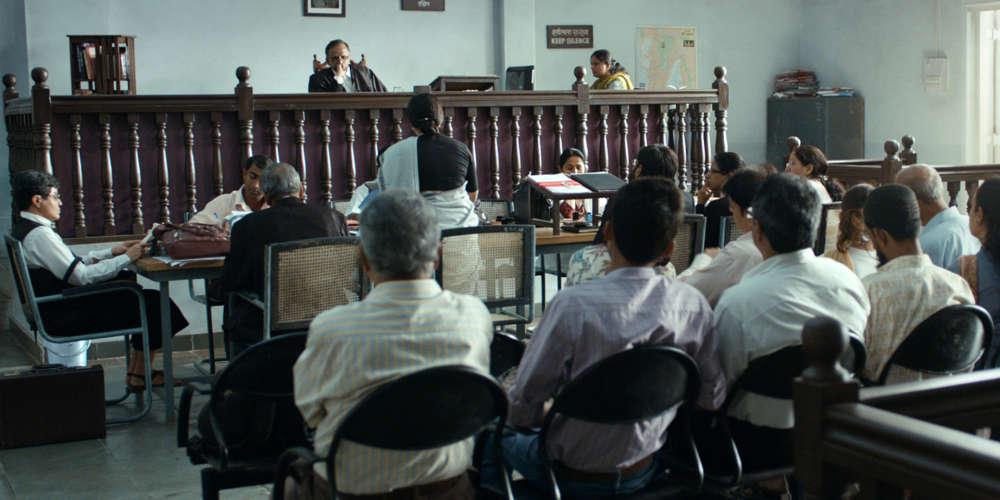 Cette fiction profondément enracinée dans le réel raconte le procès à l'époque contemporaine de Narayan Kamble, chanteur de folk contestataire fictif, inspiré par un véritable chanteur du groupe radical anti-caste des années 1970, Dalit Panther, et interprété par le chanteur et activiste Vira Sathidar. Le jeune réalisateur a puisé l'inspiration à la source, en allant assister à des procès en première instance, et en apprenant le jargon approprié dans les livres de droit.